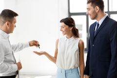 Realtor giving key to customers at new office. Real estate business, sale and people concept - realtor giving key to customers or new office owner Royalty Free Stock Images