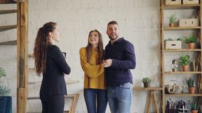 Real estate buyers are getting keys from housing agent after successful deal, kissing and hugging with happiness and. Real estate buyers are getting keys from stock video footage