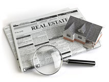 Real estate classifieds ads newspaper with house and magnifying Royalty Free Stock Image