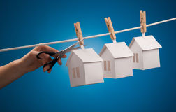 Real estate concept. Paper houses with clothespins, hanging from rope on blue background Royalty Free Stock Photos