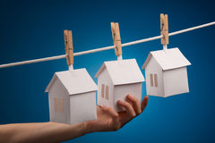 Real estate concept. Paper houses with clothespins, hanging from rope on blue background Royalty Free Stock Photo
