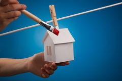Painting a paper house. Paint brush ready to paint the roof of a paper house pegged to a washing line with a blue sky background Stock Photos