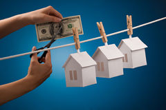Real estate concept. Paper houses with clothespins, hanging from rope on blue background Stock Images