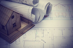 Real Estate concept. Architect workplace. Architectural project, blueprints, blueprint rolls and  model house on plans Royalty Free Stock Image