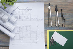 Real Estate concept. Architectural project, blueprints, blueprint rolls and  divider compass on vintage wooden table Royalty Free Stock Image