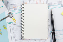 Real estate concept. Blank white notebook on architectural desk table blueprint background with key, pen, small house. Office supplies. Copy space for ad text Stock Image