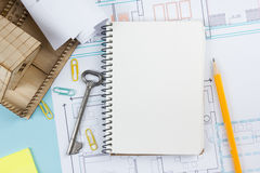 Real estate concept. Blank white notebook on architectural desk table blueprint background with key, pen, small house. Office supplies. Copy space for ad text Royalty Free Stock Image