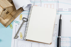 Real estate concept. Blank white notebook on architectural desk table blueprint background with key, pen, small house Stock Image