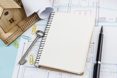 Real estate concept. Blank white notebook on architectural desk table blueprint background with key, pen, small house. Office supplies. Copy space for ad text Royalty Free Stock Images