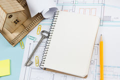 Real estate concept. Blank white notebook on architectural desk table blueprint background with key, pen, small house Royalty Free Stock Photography