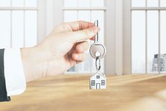 Real estate concept. Businessman hand holding key with house chain in interior with city view and sunlight. Real estate concept. 3D Rendering Stock Photos