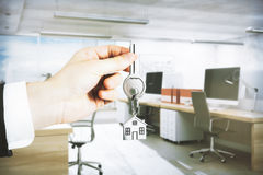 Real estate concept. Businessman hand holding key with house keychain on blurry office interior background. Real estate concept. 3D Rendering Stock Image
