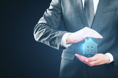 Real estate concept. Businessman holding creative glowing house icon on blue background. Real estate concept Stock Photo