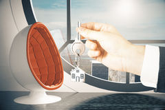 Real estate concept. Hand holding key with house keychain on modern interior background. Real estate concept. 3D Rendering Stock Images