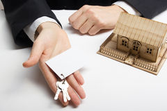 Real estate concept. Hands holding blank business card with keys. Royalty Free Stock Photography