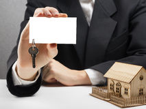 Real estate concept. Hands holding blank business card with keys. Royalty Free Stock Images