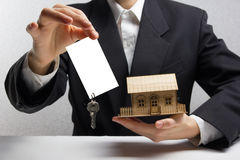 Real estate concept. Hands holding blank business card with keys. Royalty Free Stock Photo