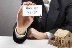 Real estate concept. Hands holding business card with text Buy or Rent and keys. Stock Images