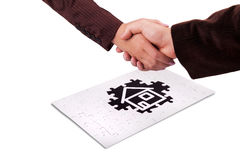 Real estate concept. Handshaking and puzzle as real estate concept Royalty Free Stock Images