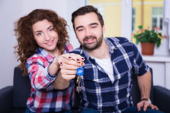 Real estate concept - happy smiling young couple showing keys of Stock Photos