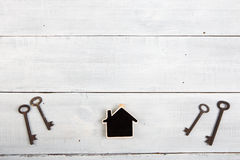 Real estate concept - little house and keys on white wooden desk Royalty Free Stock Images