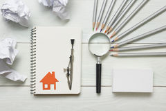 Real estate concept - magnifying glass, pencils and blank business card on wooden table. Copy space for text Royalty Free Stock Photo