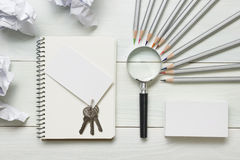 Real estate concept - magnifying glass, pencils and blank business card on wooden table. Copy space for text Stock Photo