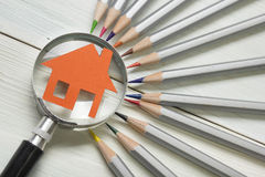 Real estate concept - magnifying glass, pencils and model house on wooden table. Stock Images