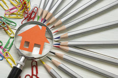 Real estate concept - magnifying glass, pencils and model house on wooden table. Stock Photography