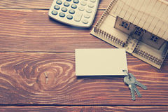 Real Estate Concept. Model house, keys, blank business card and calculator on wooden table. Top view. Toned image Royalty Free Stock Photo