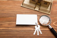 Real Estate Concept. Model house, keys, blank business card, magnifying glass on wooden table. Top view Stock Photography