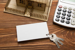 Real Estate Concept. Model house, keys, blank business card, pen and calculator on wooden table. Top view Stock Images