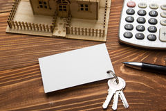 Real Estate Concept. Model house, keys, blank business card, pen and calculator on wooden table. Top view. Royalty Free Stock Photo