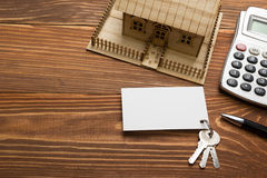 Real Estate Concept. Model house, keys, blank business card, pen and calculator on wooden table. Top view. Stock Photos