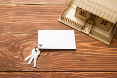 Real Estate Concept. Model house, keys, blank business card on wooden table. Top view. Model house, keys, blank business card, pen and calculator on wooden Stock Photography