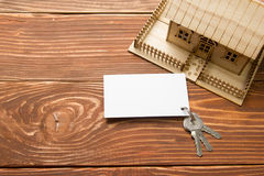 Real Estate Concept. Model house, keys, blank business card on wooden table. Top view. Toned image Royalty Free Stock Photos