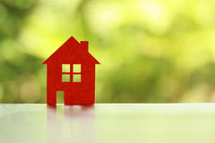 Real Estate concept. Orange paper home on green nature blur background Royalty Free Stock Photo