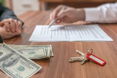 Real estate concept. Realtor agent offering the contract to sign. Money and keys on desk royalty free stock image
