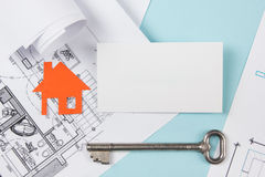 Real estate concept. Silver key with house figure and blank business card on blue background. Top view. Stock Images