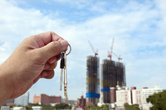 Real estate concept. Took the key. Took the key and construction of the building in the blurred background stock photos