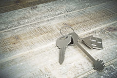 Real estate concept. Top view of metal keys with house keychain placed on aged wooden background. Real estate concept. 3D Rendering Stock Photos