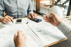 Real-estate concept, Two engineer and architect discussing blueprints data working and digital tablet on construction building. Project royalty free stock photography