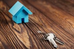 Free Real Estate Concept With Small Blue Toy Paper House And Key On Wooden Background. Idea For Real Estate Concept, Personal Propert Royalty Free Stock Image - 130698866