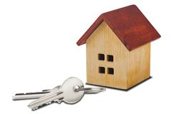 Real estate concept. Wooden house and key on isolated white background with shadows. Idea for real estate concept, personal prope royalty free stock photography