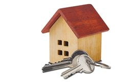 Real estate concept. Wooden house and key on isolated white background with shadows. Idea for real estate concept, personal prope stock image