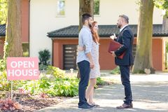 Real estate consultant inviting couple. Real estate consultant inviting young couple to see a house for rent stock photo
