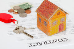 Real estate contract. With keys and house model on the document Stock Photo