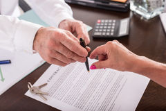 Real estate contract before signing. Realtor giving his client a pen to sign the contract Royalty Free Stock Images