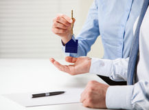 Real estate deal. Real estate agent giving keys to the customer over the table Royalty Free Stock Image