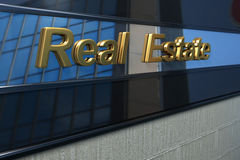 Real estate facade. Real estate word over a modern facade with reflection of a building in the mirror Royalty Free Stock Photo